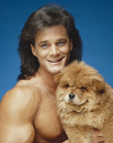 IMAGE BANK FAIL - Young man holding dog against blue background, close-up, portrait (c) Tom Kelley Archive